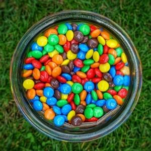 A jar of M&M's on a lawn