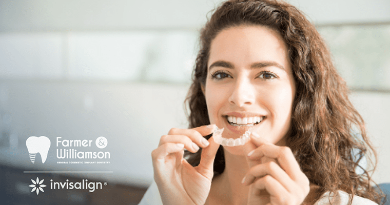 A woman holding a clear aligner addressing how does Invisalign work