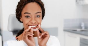 Teen girl holding up an Invisalign clear aligner